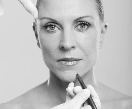 cosmetic surgeon marking mid age woman